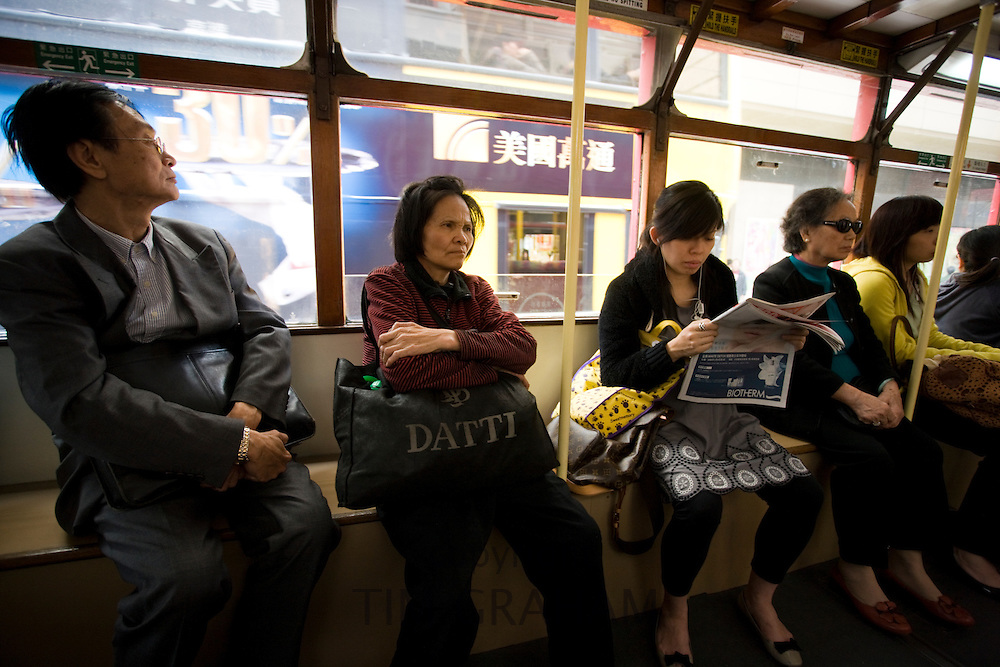 Passengers in tram in traditional old Chinese district, Des Voeux Road, Sheung Wan, Hong Kong Island, China