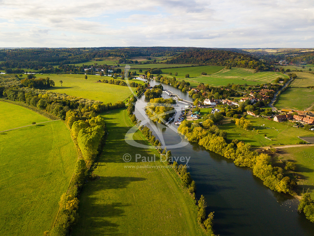 The afternoon sun illuminates the lush English landscape and the River Thames at Hambledon Lock near Henley-On-Thames, Oxfordshire as the colours of autumn behind to appear on the trees. Henley On Thames, October 01 2018.