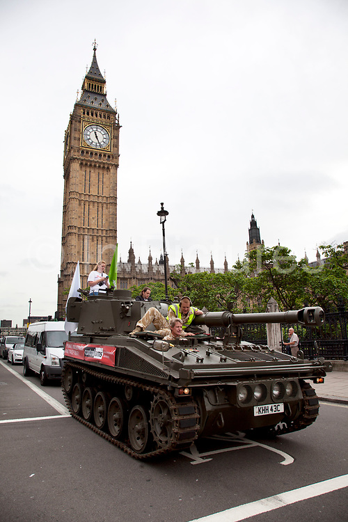 Tank passed through Parliament Square past Big Ben and the Houses of Parliament. Campaigners and supporters from Oxfam and Amnesty International, as part of the Control Arms coalition, drive an Abbot gun tank around central London to highlight the need for a global Arms Trade Treaty (ATT) to be agreed during a United Nations conference next month (July 2012). London, England, UK. 27th June 2012.