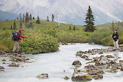 Parmenter Welty throws trekking poles to his wife Liana at a small but tricky creek crossing in Donoho Basin, Wrangell-St. Elias National Park, Alaska.