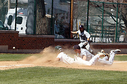 14 April 2013:  Anthony Lopez dives for the third base bag as Chris Fisher misses the pick off throw and is backed up by Kevin Bellew during an NCAA division 3 College Conference of Illinois and Wisconsin (CCIW) Baseball game between the Elmhurst Bluejays and the Illinois Wesleyan Titans in Jack Horenberger Stadium, Bloomington IL