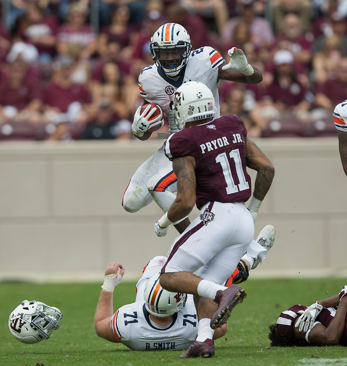Auburn running back Kerryon Johnson (21) jumps over teammate Braden Smith (71) while trying to avoid a tackle during the third quarter of an NCAA college football game on Saturday, Nov. 4, 2017, in College Station, Texas. (AP Photo/Sam Craft)