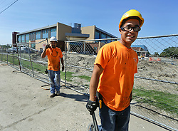 26 August 2015. New Orleans, Louisiana. <br /> Hurricane Katrina revisited. <br /> Rebuilding the Lower 9th Ward a decade later. <br /> Contractors finish another day building the $40 million Martin Luther king High School. Signs of progress in one of the hardest hit areas of the city.<br /> Photo credit©; Charlie Varley/varleypix.com.