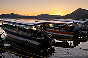 Water taxis called Pangas tied up along the shore of Lake Catemaco at sunset in Catemaco, Veracruz, Mexico. The tropical freshwater lake at the center of the Sierra de Los Tuxtlas, is a popular tourist destination and known for free ranging monkeys, the rainforest backdrop and Mexican witches known as Brujos.