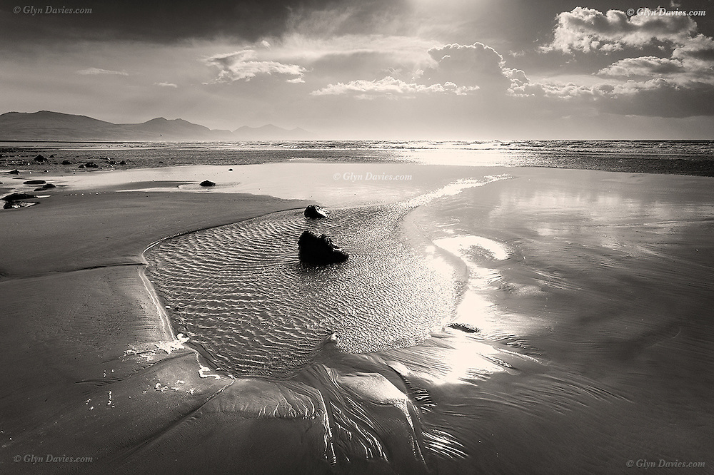 Dinas Dinlle is a vast beach beyond Caernarfon in Gwynedd North Wales. It is backed by an ancient hill fort which is gradually being eroded away by each high tide. As the tide retreats it leaves a huge expanse of sand, rocks and pools
