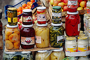 "Jars of pickled vegetables for sale at the Ciglane outdoor ""green"" market in Bosnia and Herzegovina. Signs of the four-year siege of Sarajevo are still obvious today. Although food stalls have returned to the Ciglane market, parts of the Olympic park behind it have become a burial ground for siege victims. (Supporting image from the project Hungry Planet: What the World Eats.)"