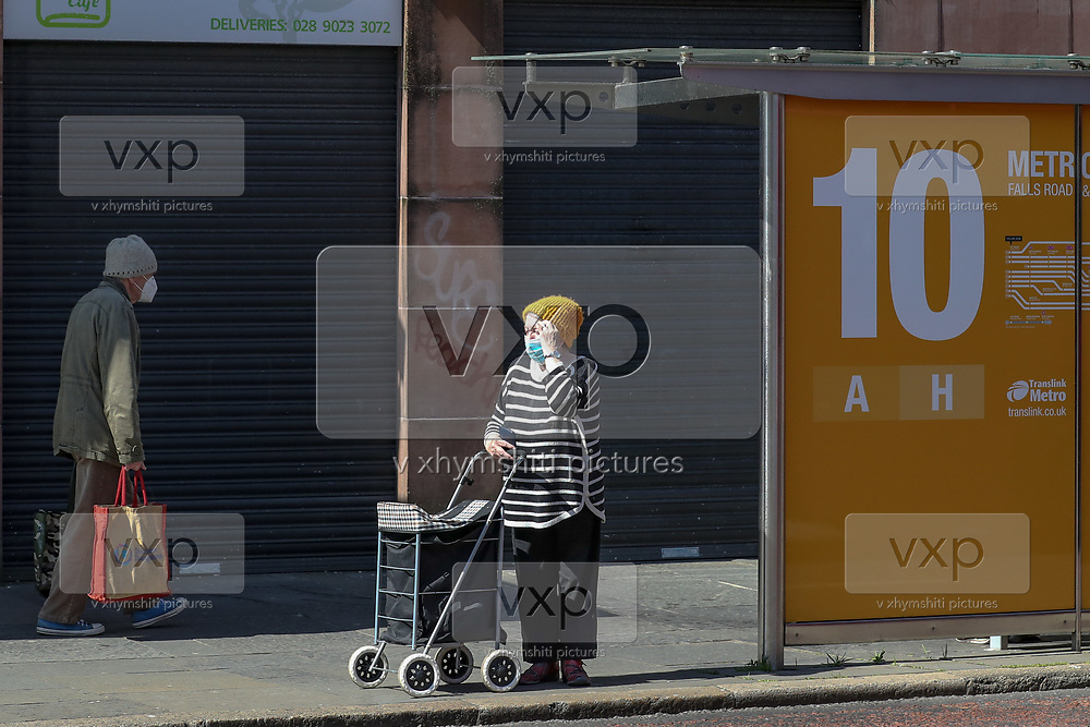 A woman wearing a face protective surgical mask awaits for the local bus in Belfast on Saturday, April 24, 2021. Thousands of people in Northern Ireland will get their first chance in months for haircuts, casual shopping and restaurant meals since Friday, as the government takes the next step on its lockdown-lifting. (Photo/ Vudi Xhymshiti)
