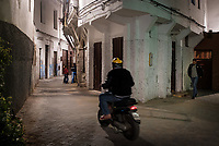 CASABLANCA, MOROCCO - CIRCA APRIL 2018: Man riding a motorcycle in he streets of the medina of Casablanca at night.