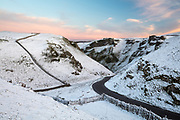 Colourful dusk skies reflect gentle light into a dramatic, snow covered Winnats Pass in the Peak District. English landscape photography in Derbyshire. Winter, January, 2016