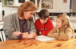Woman sitting at kitchen table with two children,