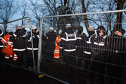 Steeple Claydon, UK. 23 February, 2021. National Eviction Team bailiffs acting for HS2 Ltd erect fencing at the end of the first day of an operation to evict activists opposed to the HS2 high-speed rail link from ancient woodland known as Poors Piece. The activists created the Poors Piece Conservation Project there in spring 2020 after having been invited to stay on the land by its owner, farmer Clive Higgins. Already, local village communities have been hugely impacted by HS2, with 550 acres of land seized including a large section of a nature reserve.