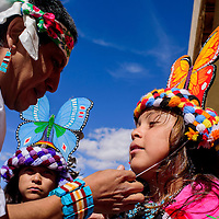 Gabriella James, right, has her headdress tied by Mangaysha Kallestewa as she and classmate Talia Wallace, center, prepare for the Zuni butterfly dance during the Indigenous Peoples' Day celebration at Six Directions School in Gallup Monday.