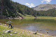 Hiker and dog play fetch in mountains of New Mexico.