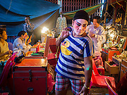 18 JANUARY 2015 - BANGKOK, THAILAND:  A performer with the Sai Yong Hong Opera Troupe walks through the backstage area before a performance at the Chaomae Thapthim Shrine, a Chinese shrine in a working class neighborhood of Bangkok near the Chulalongkorn University campus. The troupe's nine night performance at the shrine is an annual tradition and is the start of the Lunar New Year celebrations in the neighborhood. The performance is the shrine's way of thanking the Gods for making the year that is ending a successful one. Lunar New Year, also called Chinese New Year, is officially February 19 this year. Teochew opera is a form of Chinese opera that is popular in Thailand and Malaysia.             PHOTO BY JACK KURTZ