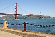 Heavy chain links with the Golden Gate Bridge and Marin County in the background.