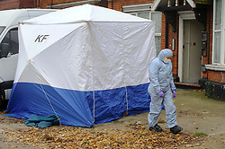 © Licensed to London News Pictures. 03/12/2013 London, UK. A forensic officer stands outside a house on the North Circular Road where a  teenager has been stabbed to death. Officers were called to the address  in Palmers Green where they found the 17-year-old from Haringey. Photo credit : Simon Jacobs/LNP