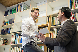 Two men looking at each other in front of bookshelf, Bavaria, Germany