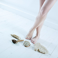 studio shot picture of a young beautiful breast naked caucasian woman lying on a white floor using bodycare tools