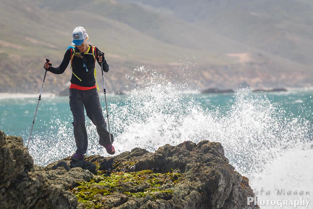 Female hiker scrambles to avoid spray from crashing waves