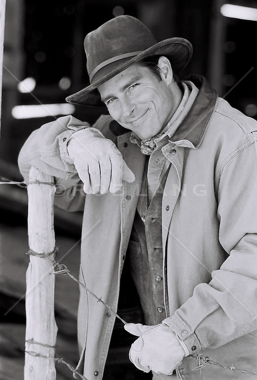smiling rancher leaning on a post
