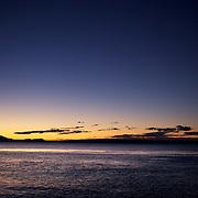 Fly fishermen fishing at sunset on the shores of Lake Toupo,,Toupo, New Zealand,, 9th January 2010 Photo Tim Clayton