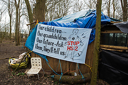 Steeple Claydon, UK. 24 February, 2021. An anti-HS2 banner is pictured in ancient woodland known as Poors Piece during an operation by Thames Valley Police to remove activists opposed to the HS2 high-speed rail link on behalf of HS2 Ltd. The activists created the Poors Piece Conservation Project there in spring 2020 after having been invited to stay on the land by its owner, farmer Clive Higgins. Already, local village communities have been hugely impacted by HS2, with 550 acres of land seized including a large section of a nature reserve.