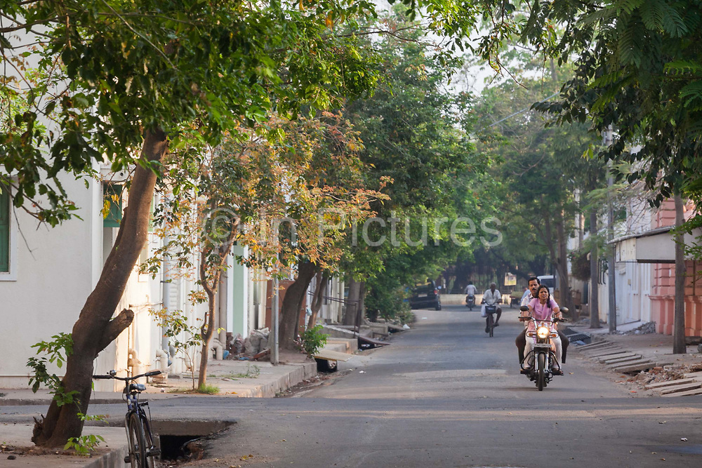 A man and a woman on a motorbike ride through the picturesque streets at dawn, Pondicherry, India<br /> Pondicherry now Puducherry is a Union Territory of India and was a French territory until 1954 legally on 16 August 1962. The French Quarter of the town retains a strong French influence in terms of architecture and culture.