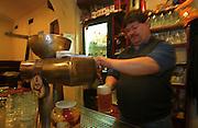 """Barmann Peter zapft ein frisches, tschechisches Bier. Aufgenommen in der Prager Szenekneipe """"Zum ausge-schossenen Auge"""" (U vystrelenyho Oka) im Stadtteil Zizkov/Prag 3. <br /> <br /> Barman Peter serves a fresh draught Czech beer. Photographed in the Prague pub """"To the shoot out eye"""" (U vystrelenyho Oka) in the quarter Zizkov/Prague 3."""