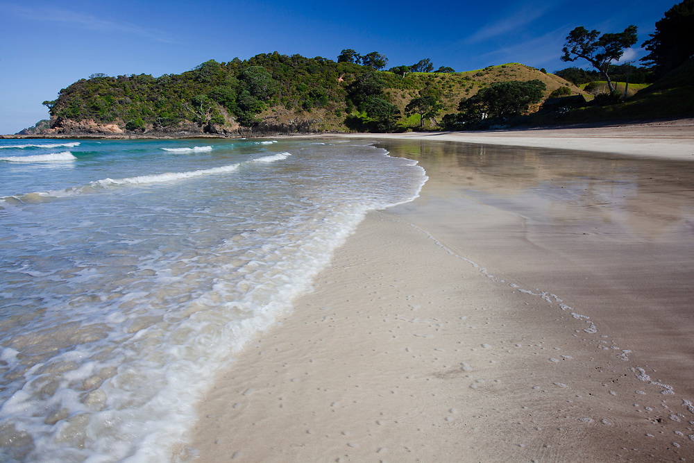 Clean ocean washes over deserted white sandy beach Moureeses Bay, a white sandy Northland beach <br /> perfect for swimming, diving, snorkelling, fishing and walks.