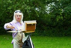 Portrait artist Robin-Lee Hall enjoys a break from her studio by painting a landscape at Rivermead Island at Sunbury. Sunbury, July 03 2019.