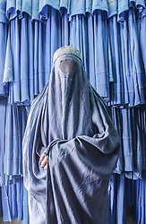 """A woman who prefers not to be identified cloaks herself inside a burqua. Afghan women were forced to wear the burqa at all times in public, because, according to one Taliban spokesman, """"the face of a woman is a source of corruption"""" for men not related to them. In a systematic segregation sometimes referred to as gender apartheid, women were not allowed to work, they were not allowed to be educated after the age of eight, and until then were permitted only to study the Qur'an."""