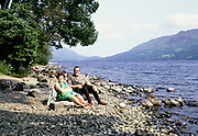 Man and woman sitting on beach at Loch Earn lake , Perthshire, Scotland  in 1968