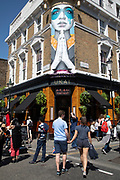 Scene outside Ukai gastropub on Portobello Road in Notting Hill, West London, England, United Kingdom. People enjoying a sunny day out hanging out at the famous Sunday market, when the antique stalls line the street.  Portobello Market is the worlds largest antiques market with over 1,000 dealers selling every kind of antique and collectible. Visitors flock from all over the world to walk along one of Londons best loved streets.