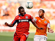 Apr 14, 2013; Houston, TX, USA; Chicago Fire forward Patrick Nyarko (14) heads a ball while defended by Houston Dynamo defender Corey Ashe (26) in the second half at BBVA Compass Stadium. The Dynamo won 2-1. Mandatory Credit: Thomas Campbell-USA TODAY Sports