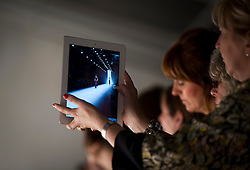 © Licensed to London News Pictures. 15/09/2012. London, UK.  A woman using her iPad to take a photograph of John Rocha catwalk show at London Fashion Week Spring/Summer 2013 on September 15, 2012. Photo credit : Ben Cawthra/LNP