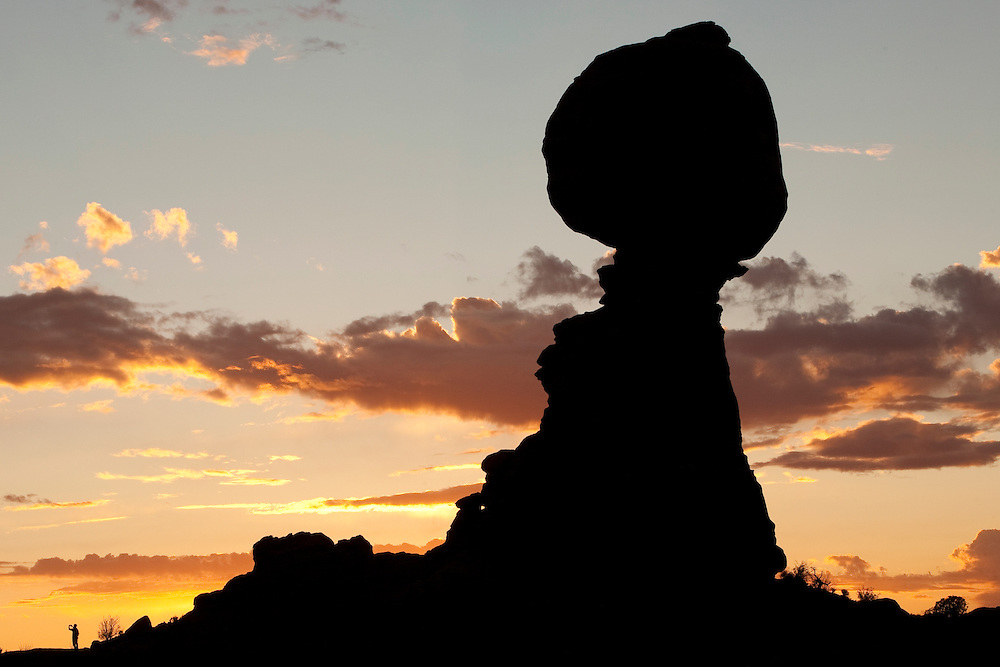 North America, United States, Utah, Arches National Park, Balanced Rock at sunset, with man taking photograph at base