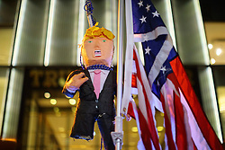 © Licensed to London News Pictures. 09/11/2016. New York, USA. Thousands of anti-Trump demonstrators protest outside Trump Tower with a Donald Trump pinata after marching from Union Square in New York City, on Wednesday, 9 November 2016 following the presidential election won by Donald Trump. Photo credit: Tolga Akmen/LNP