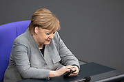 German Chancellor Angela Merkel, looks at her smartphone during a session on the Annual Economic Report for 2019 at the German parliament the Bundestag in Berlin, Germany, January 31, 2019.