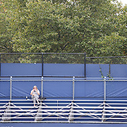 A tennis fan fins a quite corner for lunch during a rain delay at the US Open. Flushing. New York, USA. 28th August 2013. Photo Tim Clayton