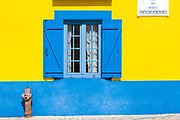 Traditional brightly coloured blue and yellow facade of property in Cais dos Botiroes harbour side by marina at Aveiro, Portugal