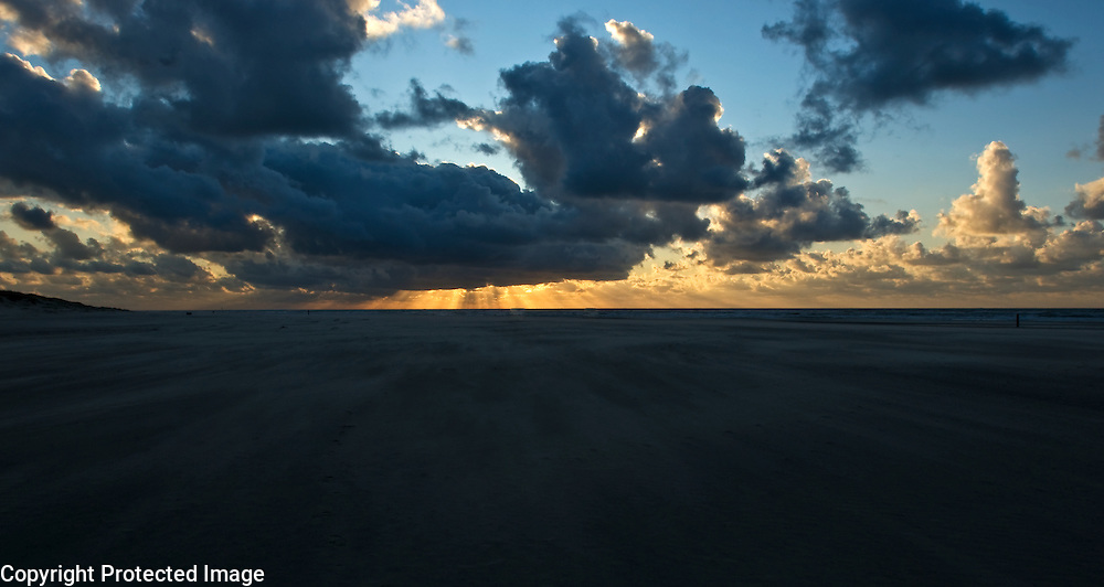 A windswept beach with sand flying towards the rays of the setting sun, Texel, the Netherlands