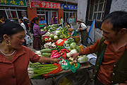 People shop for vegetables at a market in Lhasa, Tibet.