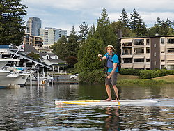 United States, Washington, Bellevue, man stand-up paddleboarding in Meydenbauer Bay  MR