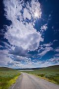 Sunburst through cumulus cloud formations over Utah highway