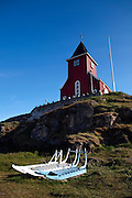 Dog sleds lying in the grass in front of the 'new' church Sisimiut, built in 1926, in the second largest town in Greenland.