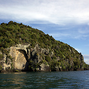 The Maori rock carvings at Mine Bay, Lake Taupo. ..Master carver Matahi Whakataka-Brightwell carved Ngatoroirangi, his first ever rock carving, onto the cliff face at the southern end of Mine Bay. The Maori rock carvings are over 10 metres high and are only accessible by boat. In the late 1970s master carver Matahi Whakataka-Brightwell came to his mother's land at Lake Taupo.  On a boat trip around the Western Bays he saw the cliffs at Mine Bay and decided to use them as a canvas for his work...Matahi decided to carve a likeness of Ngatoroirangi, a visionary Maori navigator who guided the Tuwharetoa and Te Arawa tribes to the Taupo area over a thousand years ago.  In recognition of the multi-cultural nature of New Zealand, Matahi also carved two smaller figures of Celtic design, which depict the south wind and a mermaid.  The Ngatoroirangi carving took four summers to complete and the carvers took no payment other than donations to cover the cost of the scaffolding.  The carving has become an important cultural attraction for the region. Lake Taupo, New Zealand,, 8th January 2011.  Photo Tim Clayton.