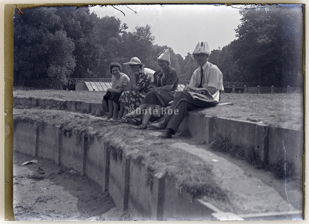 glass plate image with adults off which two wearing improvised newspaper hat