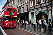 A red Routemaster London double decker bus passes Fortnum & Mason. Public transport along Piccadilly, London.