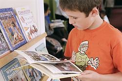 Primary school boy reading a book,