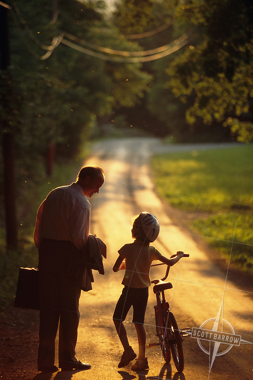 Business executive and father walking home with his bicycle riding child on a sunlit country lane.